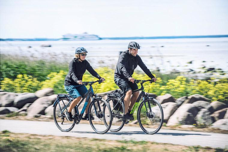 Glückliches Pärchen bei langer Radtour mit Trekking e Bikes und super Satteln.